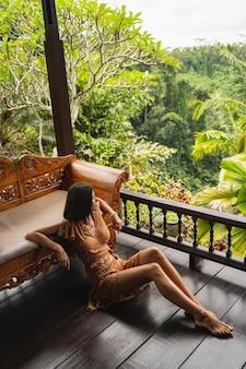Zatrzymaj chwilę. zrelaksowana młoda kobieta jest sama w bungalowie, patrząc na palmy w poszukiwaniu inspiracji