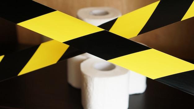 Zatrzymaj panikę - koronawirus. rolki papieru toaletowego za żółtą taśmą