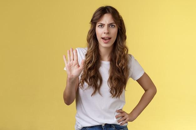 Zatrzymaj się. dziewczyna czuje intensywny poważny grymas żądania zakończenia nieprzyjemnej rozmowy podniesienie dłoni odrzucenie odmowa zabrania wystarczającej marnowania czasu marszcząc brwi rozczarowane żółtym tłem.
