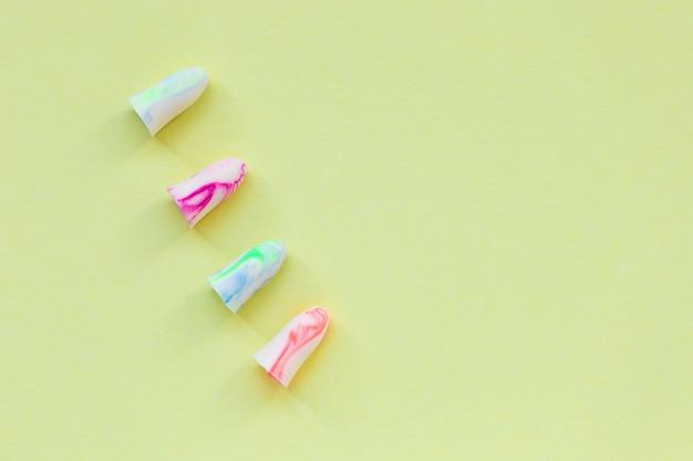 Zatyczki do uszu na żółtym. koncepcja dobrego snu i ochrony przed hałasem.