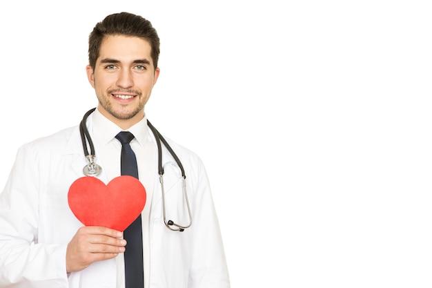 Zaufaj mu swoim sercem. portret młodego szczęśliwego przystojnego lekarza, trzymając czerwone serce i uśmiechając się radośnie na białym tle