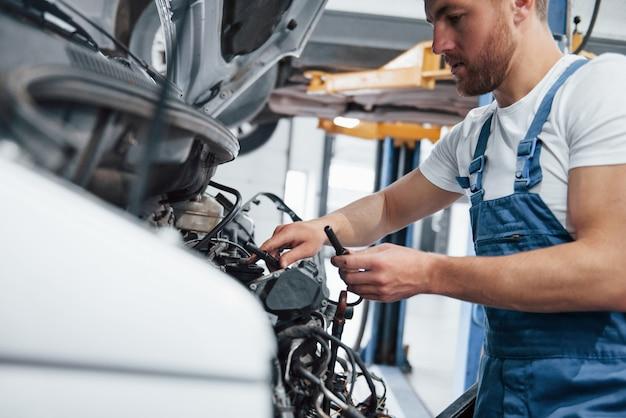 Zaufaj swojemu mechanikowi. pracownik w niebieskim mundurze pracuje w salonie samochodowym