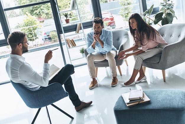 Zaufaj swojemu terapeucie. młode małżeństwo rozmawia podczas sesji terapeutycznej