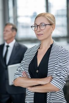 Zaufanie. blondynka w średnim wieku w okularach w pasiastej kurtce z założonymi rękami na piersi i kolegą w garniturze z laptopem z tyłu