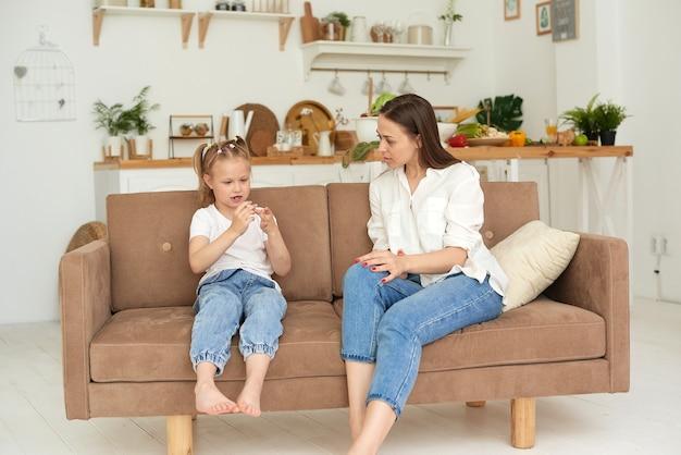 Zaufany związek mamy i córki. rozmowa kobiety z małą dziewczynką w domu na kanapie w kuchni. najlepsi przyjaciele szczęśliwy weekend macierzyństwa wraz z koncepcją dziecka.