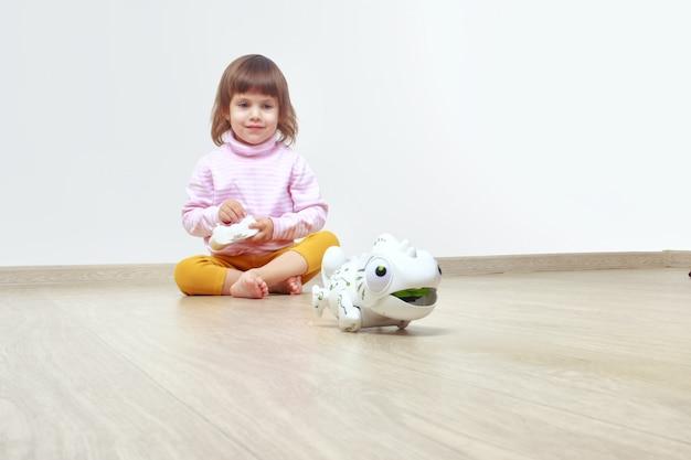 Zauroczona śliczna mała dziewczynka bawić się plastikowego zabawkarskiego robota jaszczurki z pilotem. kameleon nano-zabawkowy, nowoczesna technologia zabawek.