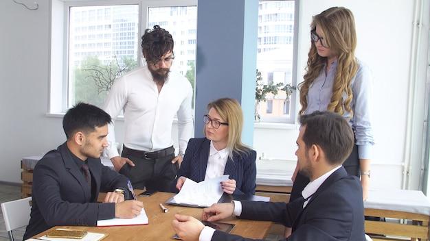 Zawarcie transakcji i podpisanie umowy o współpracy. pomyślny biznesowy mężczyzna przy spotkaniem w biurze. koledzy siedzą przy stole negocjacyjnym.