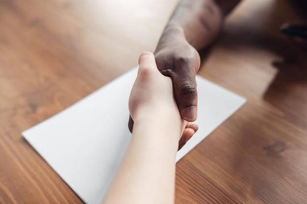 Zawarcie umowy, przyjaźń. zamknij się afro-mężczyzna i kobieta kaukaski ręce drżenie. pojęcie biznesu, finansów, pracy. miejsce na reklamę. edukacja, komunikacja i freelancer.