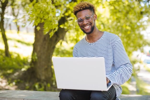 Zawartość czarny człowiek stwarzających z laptopem