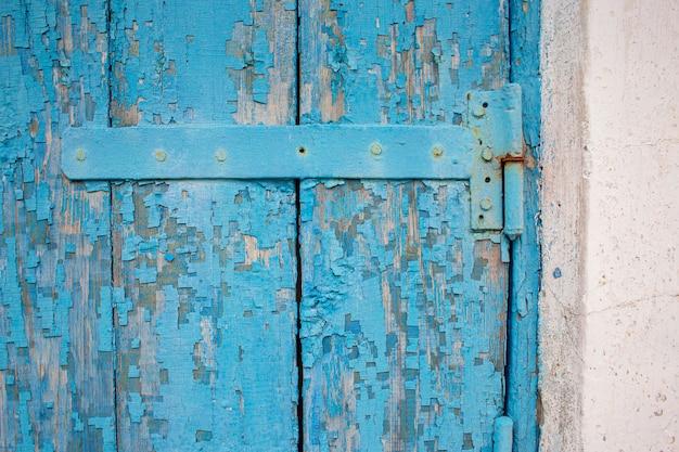 Zawias na stare drewniane drzwi z niebieską odłamaną farbą