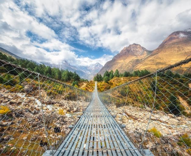 Zawieszenie most i piękne himalajskie góry przy zmierzchem w lecie