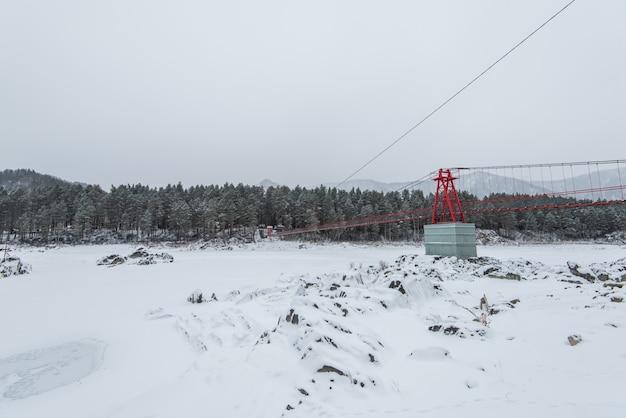 Zawieszenie wiszący most nad zima zamarznięta rzeka