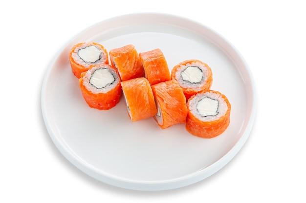 Zawijaj philadelphia z łososiem i serkiem śmietankowym. na białym talerzu ceramicznym. białe tło. odosobniony.