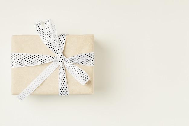 Zawijający prezenta pudełko z tasiemkowym łękiem na białym tle, kopii przestrzeń