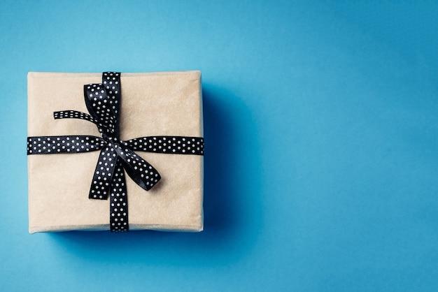 Zawijający prezenta pudełko z tasiemkowym łękiem na błękitnym tle z kopii przestrzenią