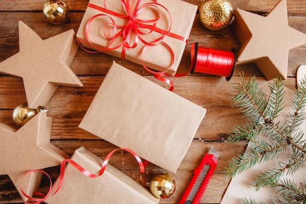 Zawijanie prezentów świątecznych w papier rzemieślniczy i czerwoną wstążkę. jest nóż biurowy, złote kulki, wstążka i gałązka jodły.