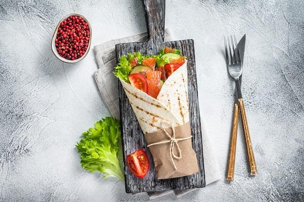 Zawiń kanapkę, bułkę z łososiem rybnym i warzywami. białe tło. widok z góry.