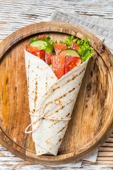 Zawiń kanapkę z łososiem, bułkę z rybą i warzywami. białe drewniane tło. widok z góry.