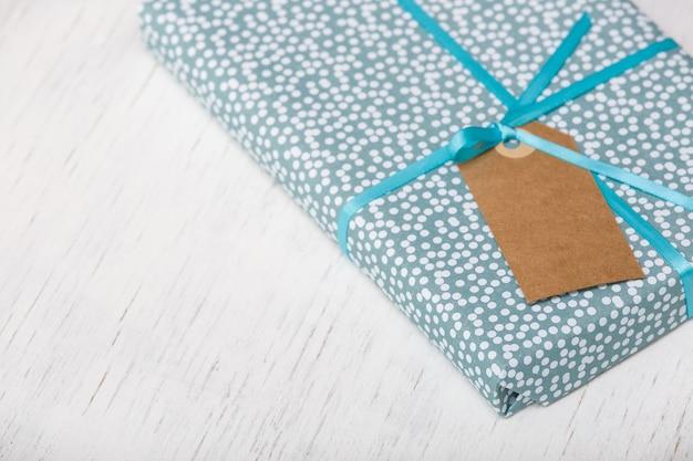 Zawinięty w papierowy prezent na urodziny boże narodzenie lub inne uroczystości na białym drewnianym tle