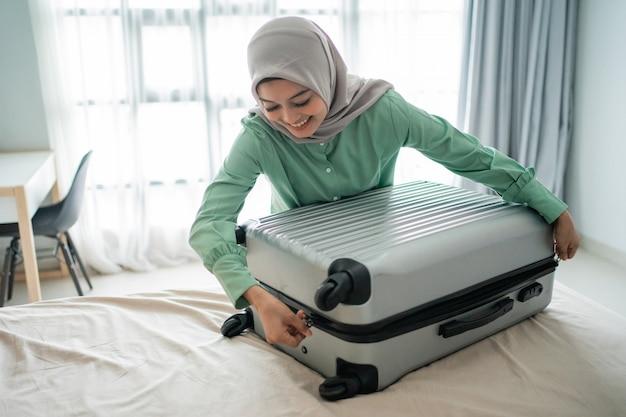 Zawoalowana kobieta próbuje zamknąć swoją pełną walizkę