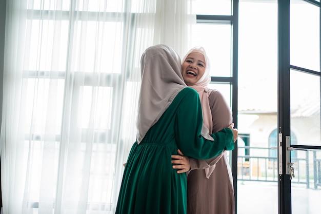 Zawoalowana kobieta przytula się i całuje siostrę podczas spotkania