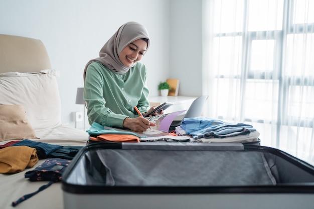 Zawoalowana kobieta siedzi na łóżku, patrząc na listę przedmiotów