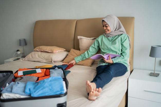 Zawoalowana kobieta siedzi na łóżku trzymając notatnik