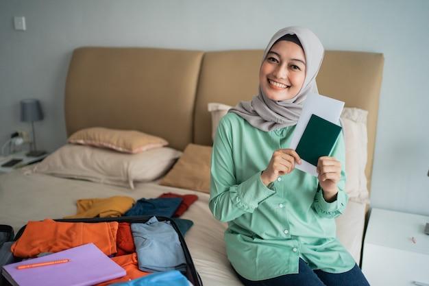 Zawoalowana kobieta trzyma bilet, podczas gdy się uśmiecha