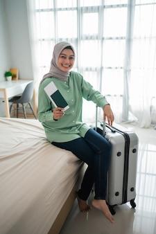 Zawoalowana kobieta trzyma bilet podczas uśmiechu