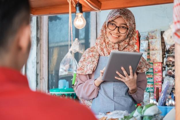 Zawoalowana sprzedawca z wózkiem uśmiecha się, obsługując klientów przy stoisku z wózkiem, używając tabletu