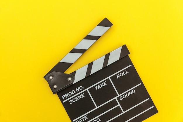 Zawód filmowca. klasycznego reżysera pusty film robi clapperboard lub filmowy łupek odizolowywający na żółtym tle. produkcja filmowa koncepcja kina przemysłowego. makieta płaski widok z góry kopia przestrzeń makieta.