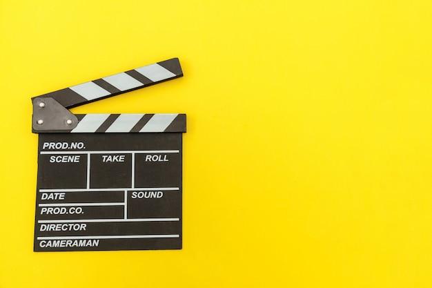 Zawód filmowca. klasyczny pusty film reżysera, który robi clapperboard lub filmowy łupek na żółtym. produkcja filmowa koncepcja kina przemysłowego. makieta płaski widok z góry kopia przestrzeń makieta.