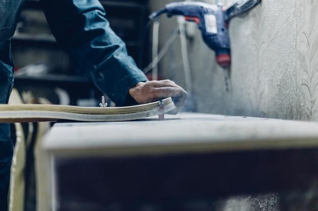 Zawód, ludzie stolarstwo, ludzie emocji koncepcja. młody rzemieślnik szlifuje talię, ponownie skupiając się za pomocą narzędzia do szlifowania