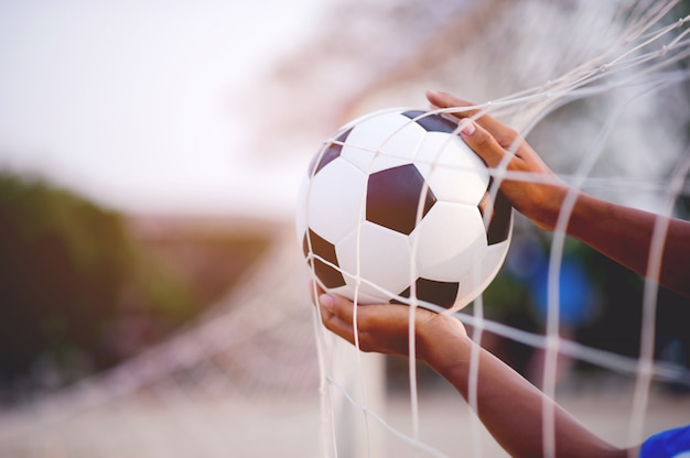 Zawodnicy sportowi, którzy łapią piłkę i boisko do piłki nożnej.