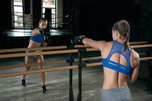 Zawodniczka w rękawicach bokserskich trenuje przed lustrem