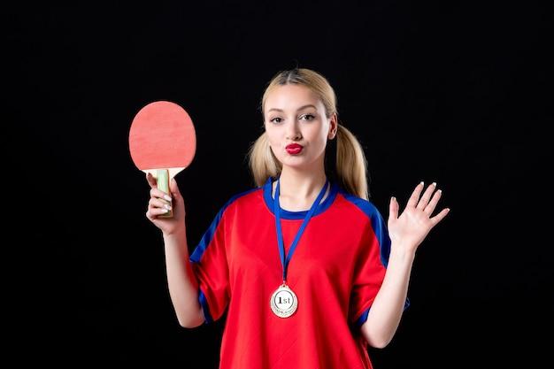 Zawodniczka z rakietą i złotym medalem na czarnym tle trofeum zwycięzcy sportowca