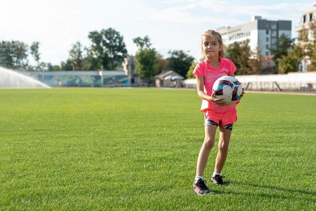 Zawodnik bez szans trzyma piłkę dziewczyna