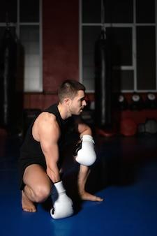 Zawodnik kickboxingu w rękawicach bokserskich stojący na kolanach.