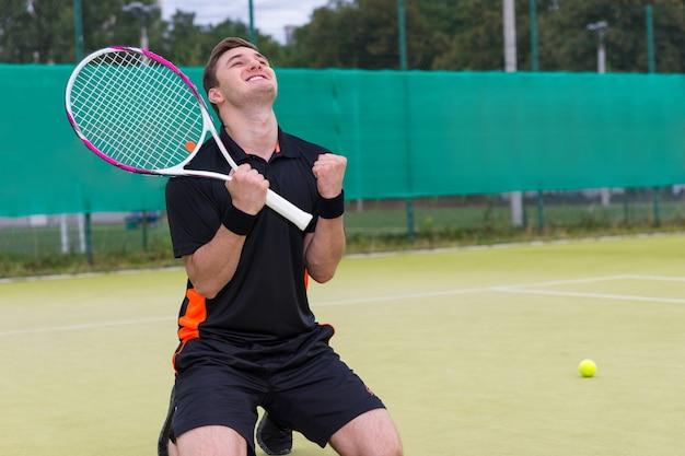 Zawodnik płci męskiej upadł na kolana i zacisnął pięść z powodu wygranej w meczu tenisowym na korcie tenisowym