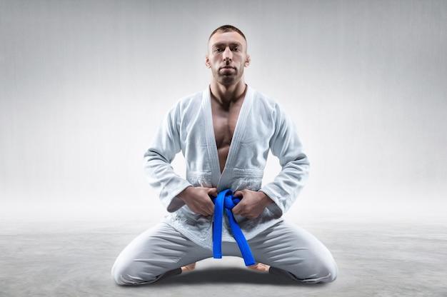 Zawodnik w kimono z niebieskim pasem siedzi i czeka na przeciwnika. koncepcja karate, sambo, jujitsu. różne środki przekazu