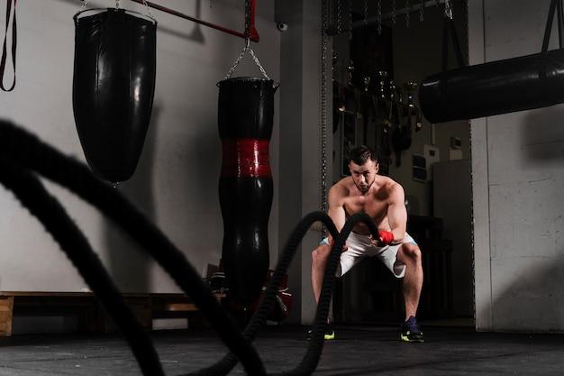 Zawodnik z dystansu, silny mężczyzna ciężko trenujący do zawodów bokserskich