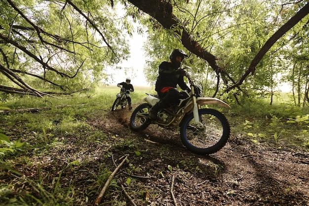 Zawodowi motocykliści w kaskach pokonujący leśne ścieżki pod niskimi gałęziami drzew podczas wyścigu terenowego