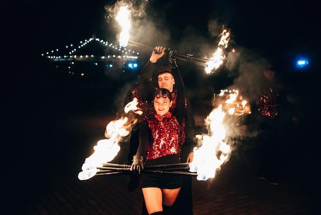 Zawodowi tancerze, kobiety i mężczyźni, organizują pokaz ognia i pokaz pirotechniczny