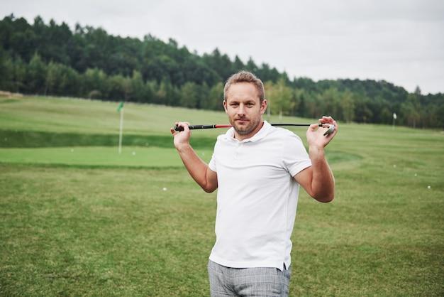 Zawodowy gracz stoi na polu golfowym i trzyma metalowy kij za plecami