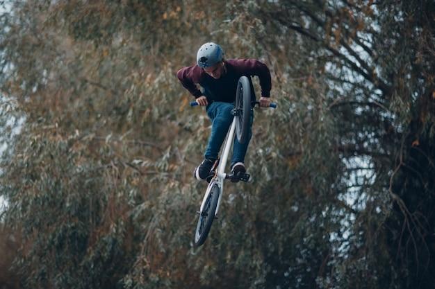 Zawodowy młody sportowiec rowerzysta z rowerem bmx robi akrobatyczne sztuczki w skateparku. młody mężczyzna bmx biker,