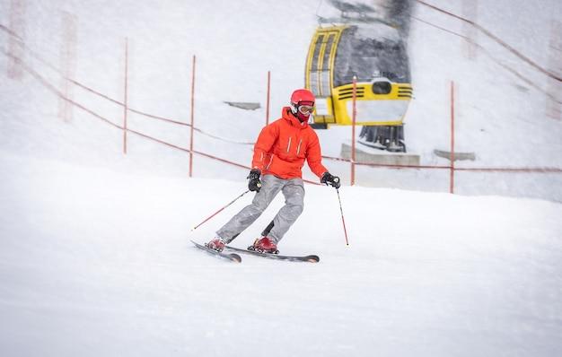 Zawodowy narciarz w czerwonej kurtce szybko zjeżdżający ze wzgórza
