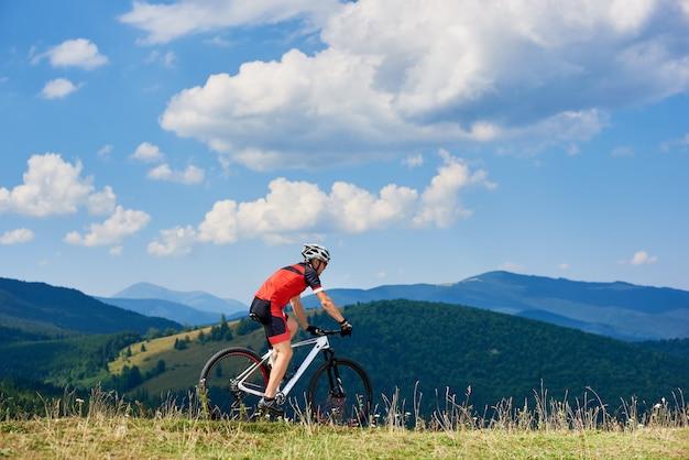 Zawodowy sportowiec rowerzysta jedzie na rowerze biegowym na wysokim trawiastym wzgórzu. piękny góra widok, chmurny niebo na tle i