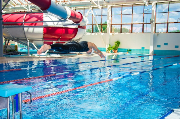 Zawodowy sportowiec skacze do wody w basenie z platformy
