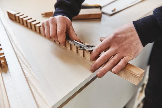 Zawodowy stolarz w pracy rzeźbi drewno za pomocą narzędzia do obróbki drewna