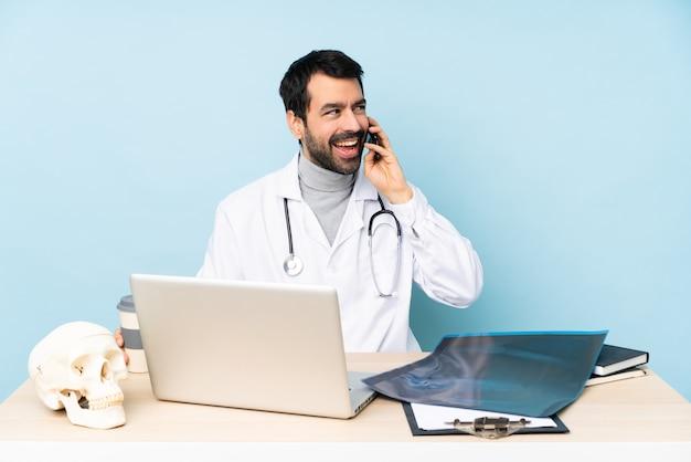 Zawodowy traumatolog w miejscu pracy prowadzący rozmowę przez telefon komórkowy